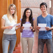 Portrait of smiling students holding a piece of paper — Stock Photo