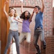 Portrait of successful students jumping — Stock Photo