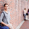 Student leaning on a wall while his friends are talking — Stock Photo