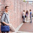 Photo: Portrait of a student leaning on a wall while his friends are talking