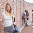 Cute student posing while her friends are talking - Stockfoto