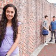 Smiling student posing while her friends are talking - Stockfoto