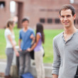 Portrait of a male student posing while his classmates are talking — Stock Photo