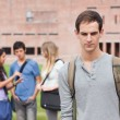Lonely student posing while his classmates are talking — Stock Photo #11193828