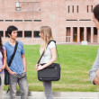Student looking at one of his classmates talking - Foto Stock