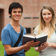 Cute couple holding a book — Stock Photo