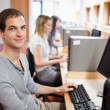 Smiling male student posing with a computer — Stock Photo #11193908