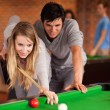 Portrait of a couple playing snooker - Stock Photo