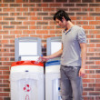 Young man recycling - Stock Photo