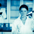 Stock Photo: Scientist dropping liquid in a test tube