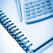 Angled notebook with pencil and pocket calculator — Stock Photo