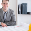 Smiling architect working on a building plan — Stock Photo
