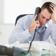 Businessman looking at an invoice while on the phone — Stock Photo