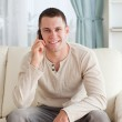 Handsome man making a phone call while sitting on a couch — Stock Photo #11196649