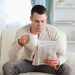 Man reading the news while drinking a coffee — Stock Photo #11196702