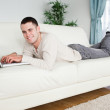 Handsome man lying on a couch with a notebook — Stock Photo #11197209