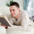 Young man lying on a couch to read a book — Stock Photo #11197214