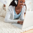 Close up of woman lying on floor with her laptop enjoying music — Stock Photo #11198322