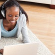 Close up of woman lying on floor with laptop listening to music — Stock Photo