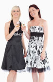 Young women in beautiful dresses with champaign — Stock Photo