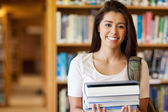 Smiling student holding books — Stock Photo