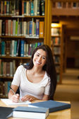 Portrait of a smiling student writing a paper — Stock Photo