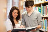 Happy students looking at a book — Stock Photo