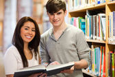 Happy students holding a book — Stock Photo