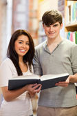 Portrait of good looking students with a book — Stock Photo