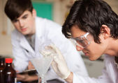 Close up of students in chemistry making an experiment — Stock Photo