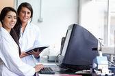 Cientista fêmea sorridente posando com um monitor — Fotografia Stock