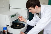 Young chemist using a centrifuge — Stock Photo