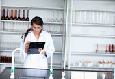 Serious female scientist writing on a clipboard — Stock Photo