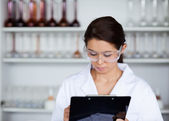 Scientist writing on a clipboard — Stock Photo