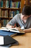 Retrato de un guapo estudiante escribir un ensayo — Foto de Stock