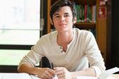 Lachende mannelijke student het schrijven van een essay — Stockfoto