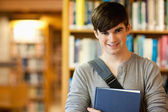 Smiling young student holding a book — Stock Photo