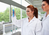 Science students looking at a graduated cylinder — Stock Photo