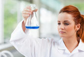Science student looking at a blue liquid — Stock Photo