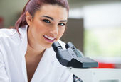 Close up of a scientist posing with a microscope — Stock Photo