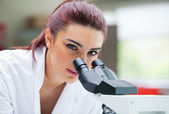 Close up of a young scientist posing with a microscope — Stock Photo