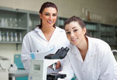 Science students posing with a microspcope — Stock Photo