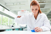 Red-haired focused scientist pouring liquid in a flask — Stock Photo