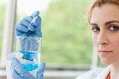Scientist dropping liquid in a beaker — Stock Photo