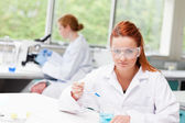 Science student dropping blue liquid in a beaker — Stock Photo