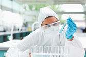 Protected scientist looking at a test tube — Stock Photo