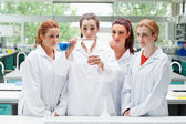 Science students pouring liquid in a flask — Stockfoto
