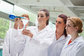 Female science students pouring liquid in a flask — Stock Photo