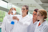Cute science students pouring liquid in a flask — Stock Photo