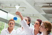 Science students looking at a flask — Stock Photo
